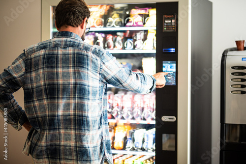 Obraz na plátně Back view of adult mature man choosing snacks and drinks on 24h free automated d