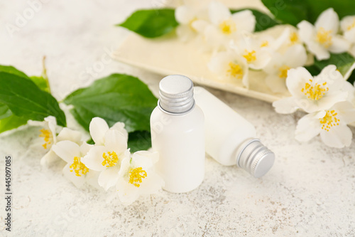 Fotografie, Obraz Bottles of cosmetic products and jasmine flowers on light background