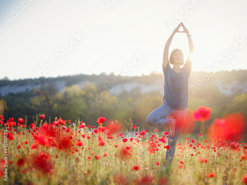 Canvas A beautiful woman meditates on a poppy field at sunset