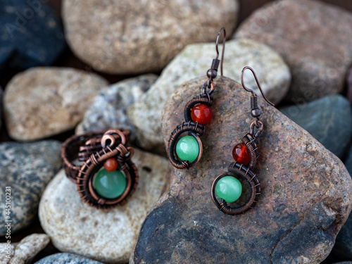Fotografie, Obraz Unique handmade jewelry ring and earrings made of wrapped copper wire and colourful stones red jasper or cornelian and green chrysoberyl cats eye lying on natural stones