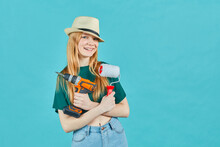 Beautiful Girl Wearing A Straw Hat With An Electric Screwdriver And An Paint Roller On Blue Background. Instruments Accessories For Renovation Apartment Room. Repair Home Concept.