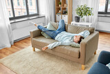 people, boredom and depression concept - lazy young man sleeping on sofa at home