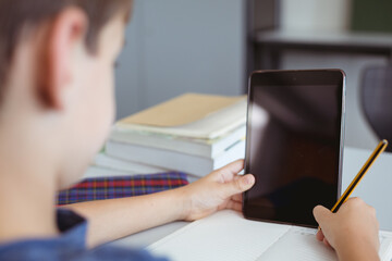 Caucasian schoolboy in classroom sitting at desk using tablet, with copy space on screen
