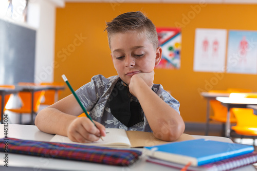 Fototapeta premium Caucasian schoolboy with face mask sitting in classroom concentrating and writing in schoolbook