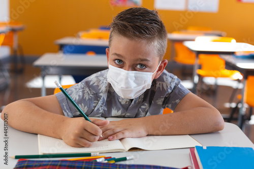 Portrait of caucasian schoolboy wearing face mask sitting at desk in classroom writing in book