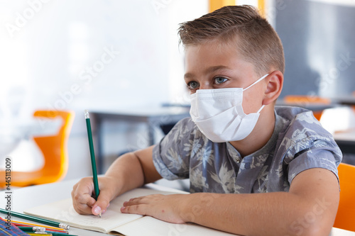 Caucasian schoolboy wearing face mask sitting at desk in classroom writing in book