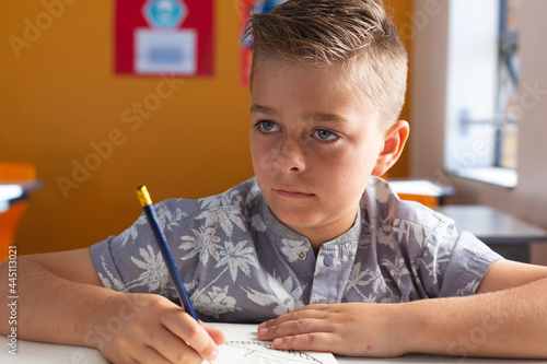Caucasian schoolboy sitting at desk in classroom writing in book during lesson