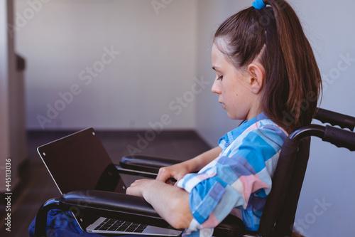 Disabled caucasian schoolgirl sitting in wheelchair using laptop in school corridor