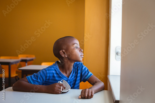Fototapeta premium African american schoolboy holding face mask sitting at desk looking out of window in classroom