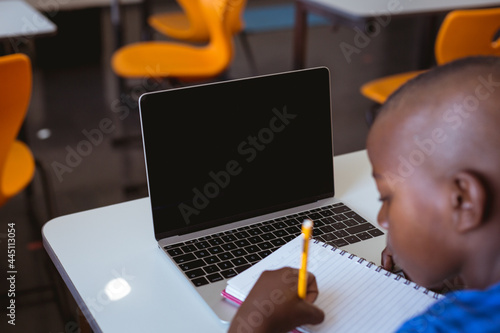 African american schoolboy sitting in classroom writing and using laptop, with copy space on screen