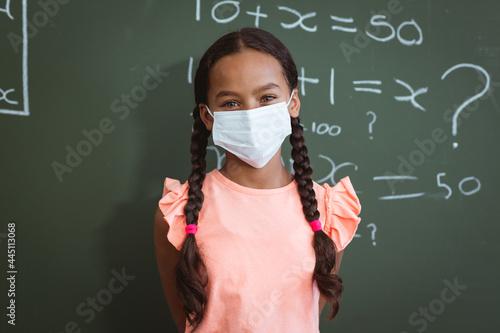 Fototapeta premium Portrait of mixed race schoolgirl in face mask standing in front of chalkboard in maths classroom