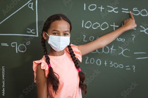 Fototapeta premium Portrait of mixed race schoolgirl in face mask standing in front of chalkboard pointing in classroom