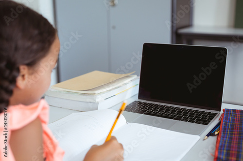 Mixed race schoolgirl sitting in classroom writing and using laptop, with copy space on screen