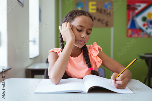 Mixed race schoolgirl in classroom sitting at desk concentrating and writing in book