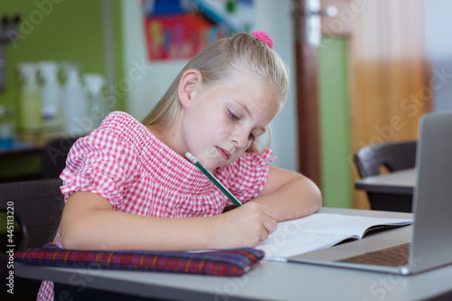 Caucasian schoolgirl at desk in classroom writing and using laptop