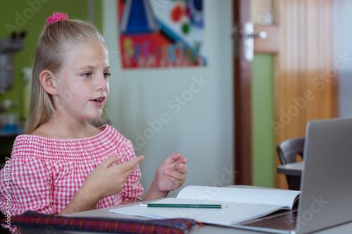 Caucasian schoolgirl at desk in classroom talking and using laptop