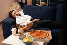 Caucasian Female Falling Asleep After Eating Junk-food In Living Room Late At Night During Takeaway Food Home Delivered. Tasty Delicious Meal Lunch Order. Unhealthy Snack Fastfood