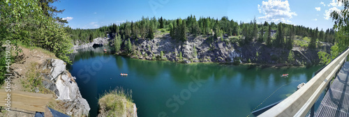 Photo Panorama with a view of the rocks, the grotto and the emerald water of the Marble Canyon in the Ruskeala Mountain Park, where boats float and the sky and trees are reflected on a sunny summer day