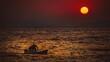 Pływający ludzie na morzu na tle ogromnego zachodzącego słońca
