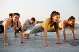 Fitness, sport, friendship and healthy lifestyle concept. Group of happy people exercising outdoor.