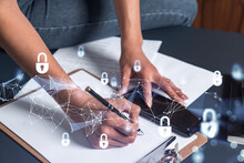 A Woman Dev Member Is Taking Notes Of Clients Needs To Protect Cyber Security From Hacker Attacks And Save Clients Confidential Data. Using Smart Phone. Padlock Hologram Icons. Casual Wear