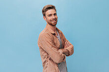 Charming Guy With Ginger Beard In Modern Shirt Looking Into Camera And Posing With Arms Crossed On His Chest On Blue Backdrop..