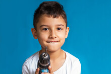 Boy Holds A Screwdriver On A Blue Background. A Student Studies The Work Of Tools