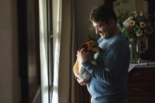 Smiling Caucasian Man Standing Standing At Window In Living Room, Petting Dog