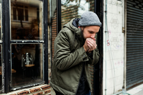 Fotografia Shivering man outdoors in a cold weather warming his hands