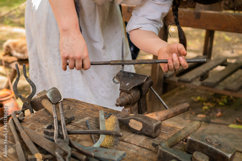 Canvas Print Professional blacksmith woman in historical costume working with metal on anvil at outdoor workshop - close up view