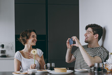 Young Couple Two Woman Man 20s In Casual Clothes Sit By Table Eat Pancake Boyfriend Take Photo Girl By Mobile Cell Phone Hold Flower Cook Food In Light Kitchen At Home Together Healthy Diet Concept