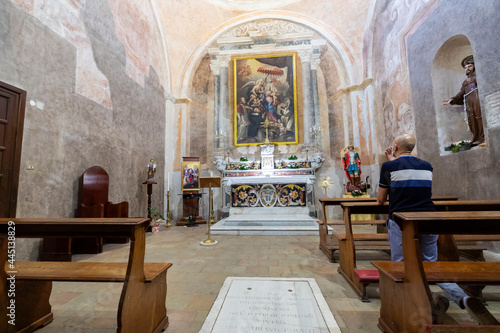 Foto Italy. Caserta. A Catholic believer prays in a church.