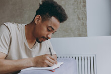 Young Smart Student African American Man 20s Wear Beige T-shirt Sit On Grey Sofa Near Heating Battery Indoors Apartment Writing In Notebook, Prepare Before Exam Resting On Weekends Staying At Home