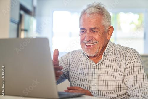 Senior Mann hat Spaß am Zoom Videochat am Computer Fototapet