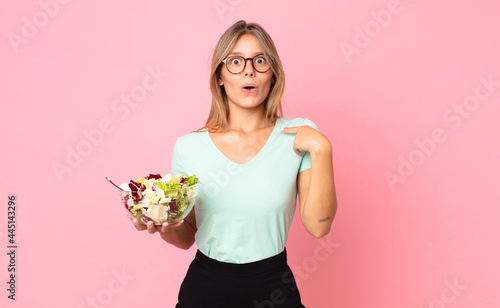Tela young blonde woman looking shocked and surprised with mouth wide open, pointing
