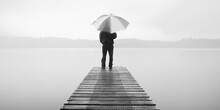 Man Holding An Umbrella On A Jetty By Tranquil Lake.