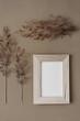 Ein leerer Holz Bilderrahmen und getrocknete Pflanzen auf einem braunen Hintergrund. Stillleben, Flat lay.