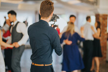 Shallow Focus Of A Young Photographer Filming A Wedding In A Restaurant