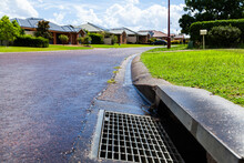 A Stormwater Drain In Gutter Of Suburban Street