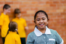 Portrait Of Happy Young Aussie School Girl Of Filipino Ethnicity Smiling And Wearing A Dress