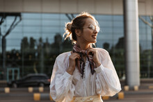 Blonde Woman Touches Her Silk Brown Scarf. Attractive Young Girl In Eyeglasses And White Blouse Smiles Outside.