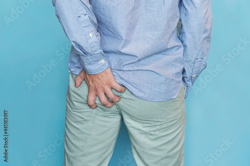 Fotografie, Obraz Man with hemorrhoids holding his ass in pain, in blue background