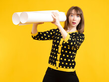Woman Is Surprised By What She Sees. She Saw Something Unusual. Portrait Of Woman With A Surprised Expression On Her Face. Girl Is Holding Binoculars Made Of Paper. Surprised Woman Yellow Background