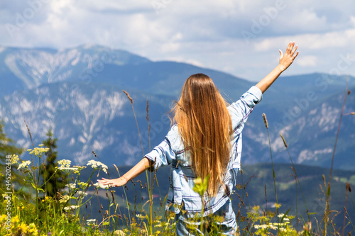 Fototapeta Girl with raised hands uphill on a background of mountains.