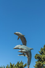 Cayucos, CA, USA - June 10, 2021: Closeup Of Jumping Dolphins On Statue At Base Of Pier Against Blue Sky.