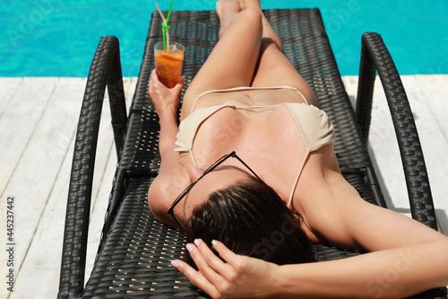 Murais de parede Beautiful woman in bikini with cocktail on sunbed near swimming pool