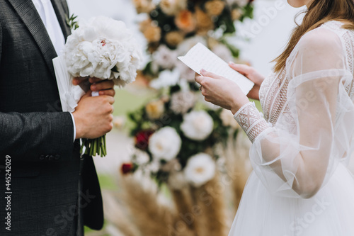 The bride and groom stand in nature at the wedding ceremony and read the oath from a sheet of paper Fototapet