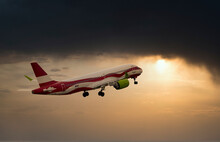 Sunset Airplane Travel. Airliner Against The Setting Sun.