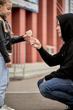 Maniac Kidnapper With Evil Face Offering Lollipop To Child Girl On City Street. Adult Man Giving Lollies To Little Kid. Concept Of Pedophilia And Kidnapping Danger To Children Left Alone.side View