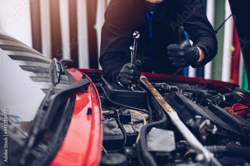 Fototapeta Car mechanic showing thumb up ok gesture in car service